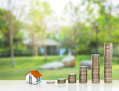 A small house sits next to stacks of coins that increase in size similar to a rising bar graph representing raising home value.