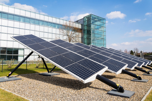 Solar panels face the sky in front of an office building.